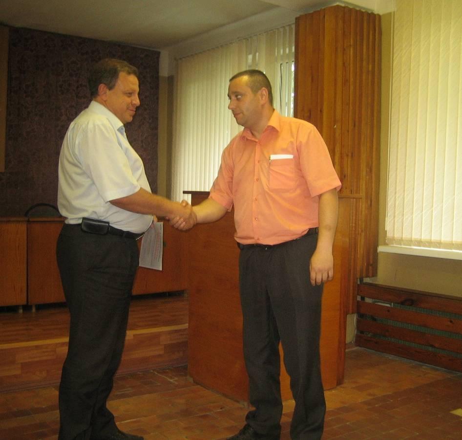 Генеральный директор Ю.А. Черняк вручает сертификат победителю внутризаводского производственного соревнования начальнику цеха ходовых частей А.Г. Болотину.